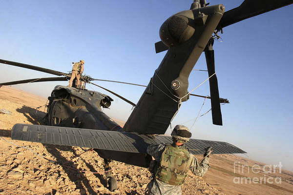Utility Aircraft Photograph - Soldiers Prepare A Uh-60 Black Hawk by Stocktrek Images
