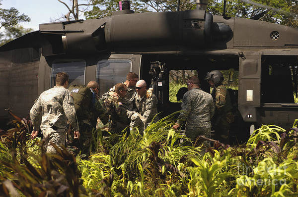 Utility Aircraft Photograph - U.s. Army Soldiers Load A Patient Onto by Stocktrek Images
