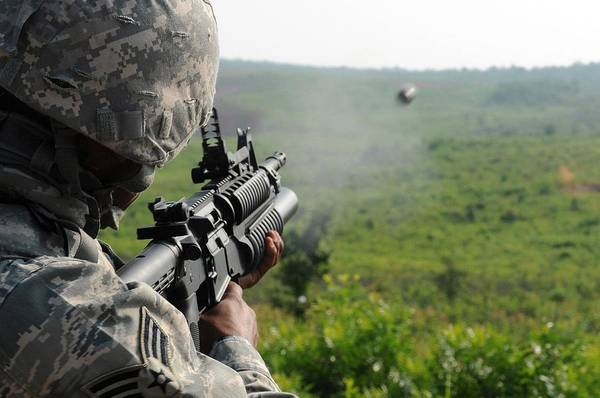 Grenade Launcher Wall Art - Photograph - Us Soldier Fires A Practice Round by Everett
