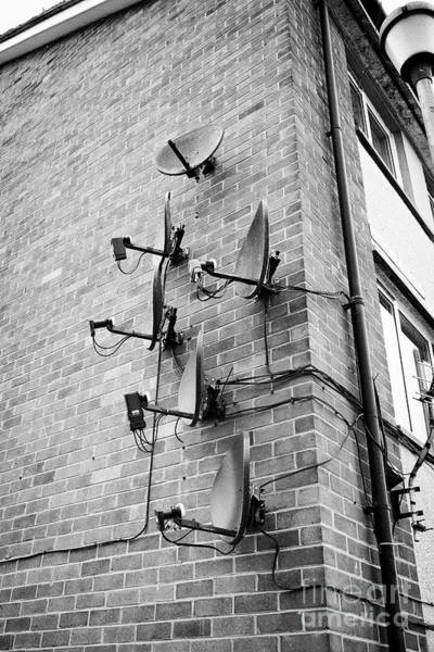 Wall Art - Photograph - Array Of Old And New Satellite Television Receiver Dishes On The Wall Of An Apartment Block Of Flats by Joe Fox