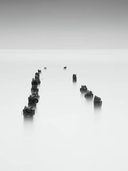 Outdoor Wall Art - Photograph - Damaged Wooden Poles Of An Old Pier In The Ocean. by Michalakis Ppalis