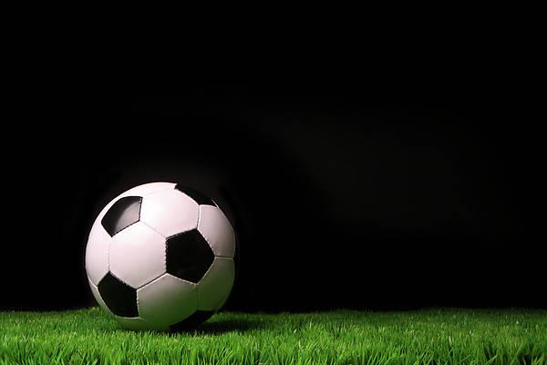 Wall Art - Photograph - Soccer Ball On Grass Against Black by Sandra Cunningham