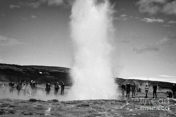 Wall Art - Photograph - tourists photograph strokkur geyser erupting at geyser geothermal site Geysir Iceland by Joe Fox