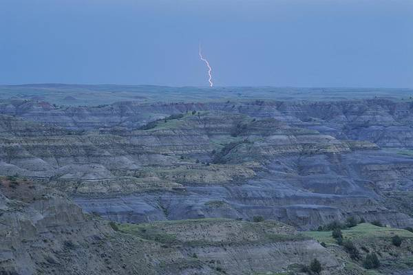 North Dakota Badlands Wall Art - Photograph - A Bolt Of Lightning Is Seen by Michael Melford