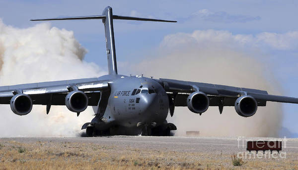 Airbase Photograph - A C-17 Globemaster Lands On The Runway by Stocktrek Images