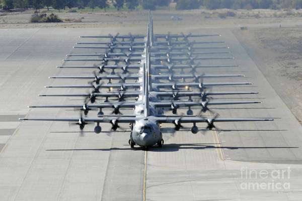 Airbase Photograph - A Line Of C-130 Hercules Taxi At Nellis by Stocktrek Images