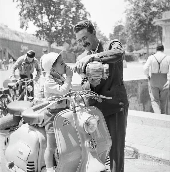 Wall Art - Photograph - A Man And His Son On A 1955 Lambretta Scooter, Drinking Water At by The Harrington Collection
