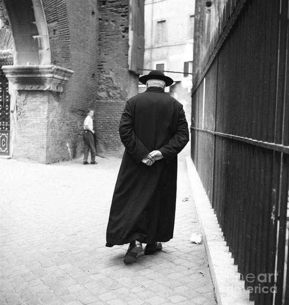 Wall Art - Photograph - A Priest Walks Down A Street In Rome, 1955 by The Harrington Collection