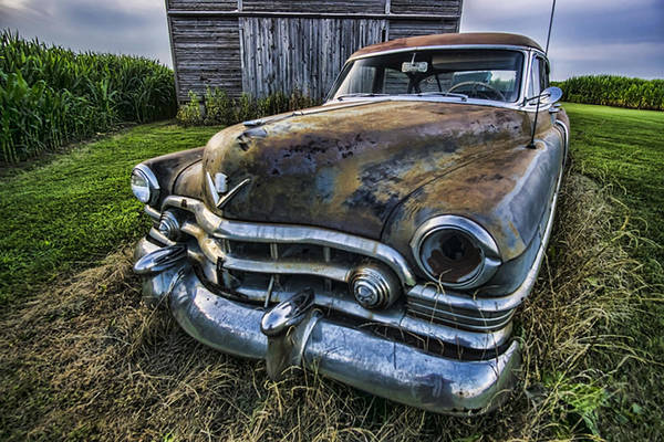Photograph - A Stylized Wide Angle Look At An Old Rusty Cadillac By A Cornfield by Sven Brogren