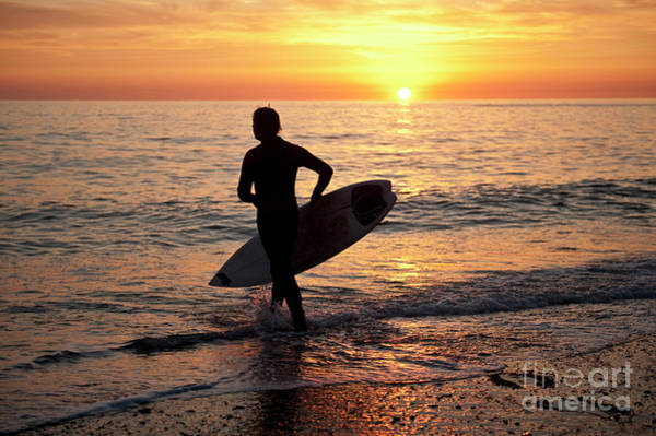 A Young Man Surfing At Sunset Off Aberystwyth Beach, Wales Uk Art Print