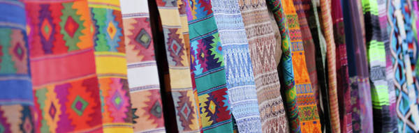 Wall Art - Photograph - An Assortment Of Colorful Blankets Hanging In A Row by Derrick Neill