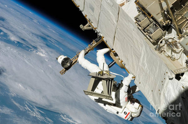 Photograph - An Astronaut Crawls Along A Truss by Stocktrek Images