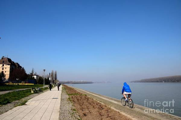 Photograph - Bicyclist And Senior Couple At Bank Of Sava River Belgrade Serbia by Imran Ahmed