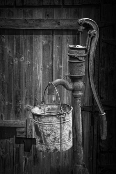 Photograph - Black And White Still Life Of Rusty Water Pump With Bucket by Randall Nyhof