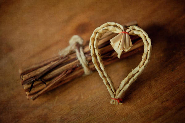 Love Photograph - Braided Wicker Heart On Small Bundled Wood by Alexandre Fundone