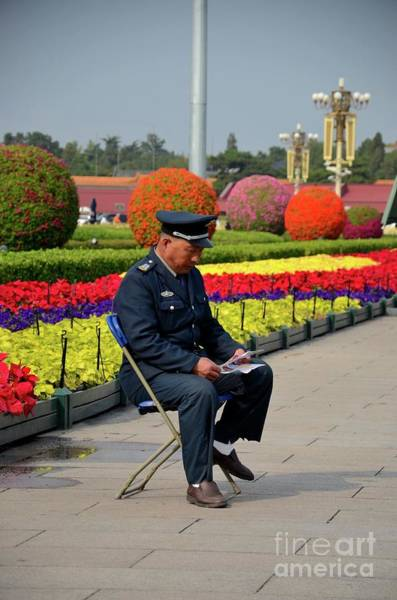 Photograph - Chinese Security Guard Reads In Front Of Flower Display Beijing China by Imran Ahmed