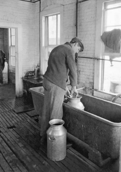 Trough Wall Art - Photograph - Dairy Farmer At Work by Underwood Archives
