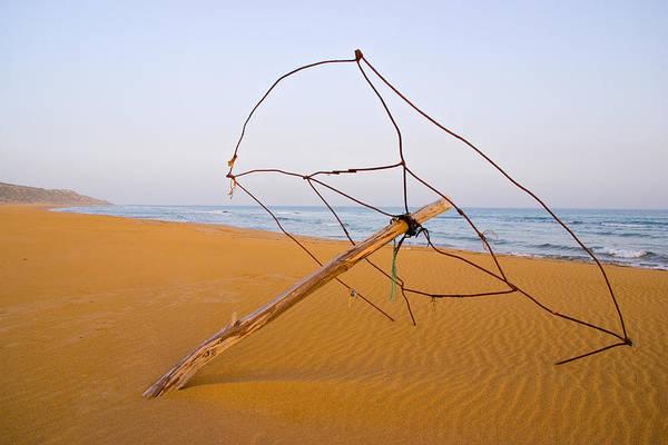 Sea Wall Art - Photograph - Derelict Umbrella On Deserted Beach by Iordanis Pallikaras