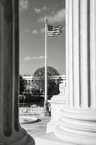 Photograph - Flag Flying Between Two Pillars Of The Supreme Court Of The Unit by Brandon Bourdages