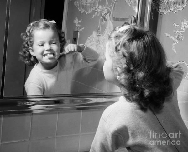 Photograph - Girl Brushing Teeth In Mirror, C.1950s by Debrocke ClassicStock