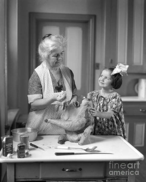 Elder Care Photograph - Girl Helping Grandmother Stuff Turkey by H. Armstrong Roberts/ClassicStock