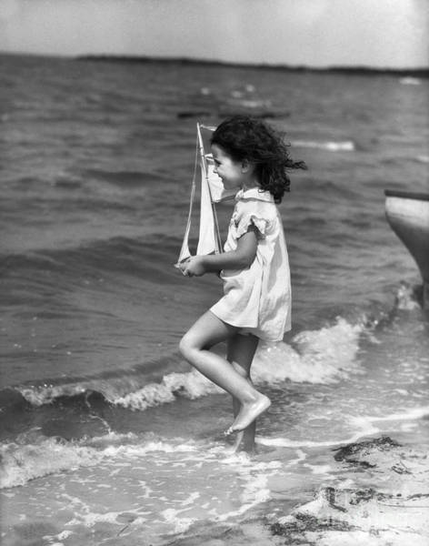 Photograph - Girl With Toy Sailboat At Seashore by H Armstrong Roberts and ClassicStock