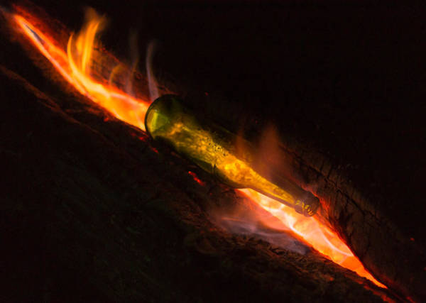Photograph - Green Glass Bottle And Campfire by John Williams