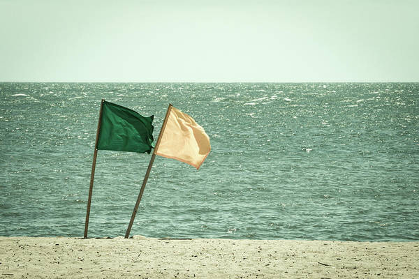Photograph - Lifeguard Flags On A Windy Day At The Beach - Faded Retro Film Look by Kyle Lee