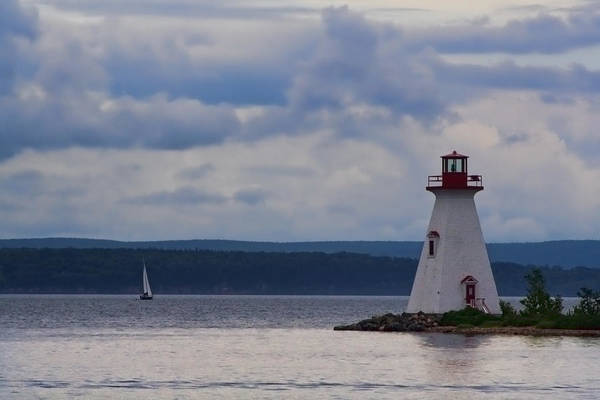 Photograph - Lighthouse And A Sail Boat In Nova Scotia by Sven Brogren