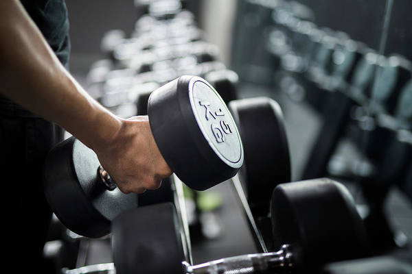 Olympic Club Photograph - Man Use Weight Training In Fitness Center by Anek Suwannaphoom