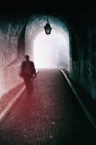 Archway Photograph - Man Walking Through A Tunnel by Carlos Caetano