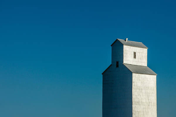 Photograph - Old Grain Elevator Against Steel Blue Sky by Todd Klassy