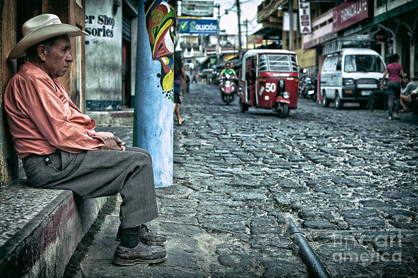 Photograph - Old Man Sitting On An Cobblestone Street With Traffic Driving By by Sam Antonio Photography