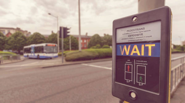 Photograph - Pedestrian Wait Sign At Pelican Crossing In Both English And Welsh Languages by Jacek Wojnarowski