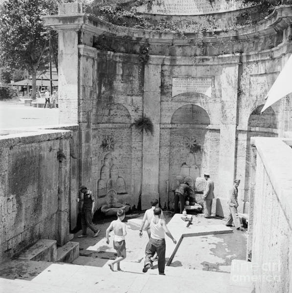 Wall Art - Photograph - People Gathering Water At A Small Fountain In Rome, 1955 by The Harrington Collection