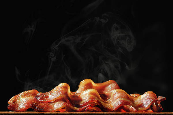 Wall Art - Photograph - Pile Of Sizzling Bacon Isolated On Black by Susan Schmitz