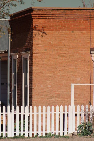 Photograph - Red Brick Building And White Picket Fence by Colleen Cornelius