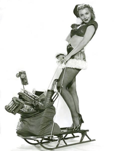 Wall Art - Photograph - Sexy Pin-up Girl On Sledge, With Bag Full Of Presents by Long Shot