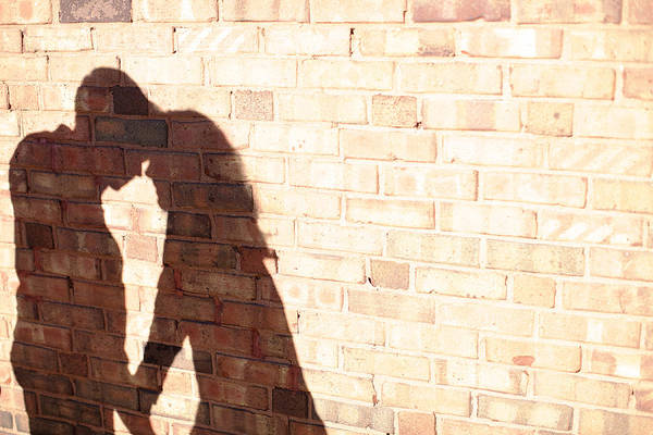 Wall Art - Photograph - Shadow On Brick Wall Of Couple by Gillham Studios