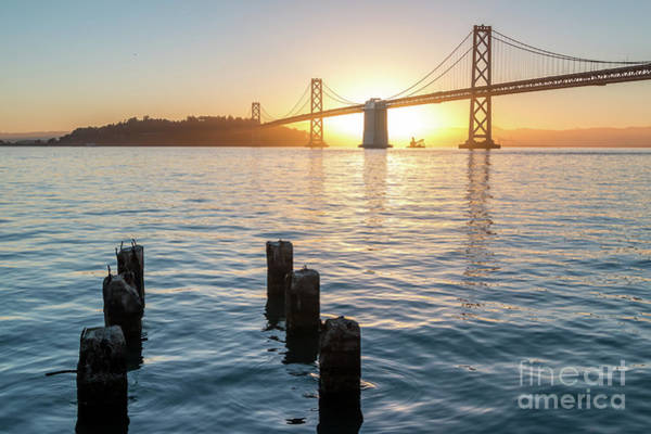Six Pillars Sticking Out The Water With Bay Bridge In The Backgr Art Print