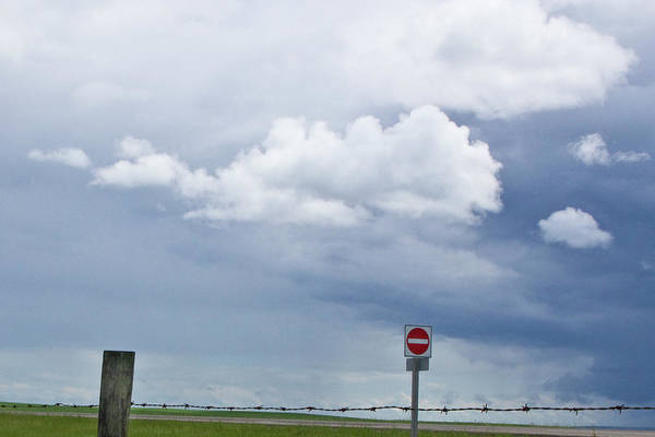 Photograph - Storm Clouds With Barb Wire Fence And Road Sign Along The Highway In Saskatchewan Canada by Randall Nyhof