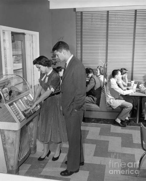 Photograph - Teen Couple Playing Jukebox, C. 1950s by H. Armstrong Roberts/ClassicStock