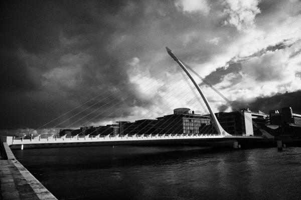 Wall Art - Photograph - the new Samuel Beckett Bridge across the river liffey in Dublin republic of ireland under dark grey  by Joe Fox