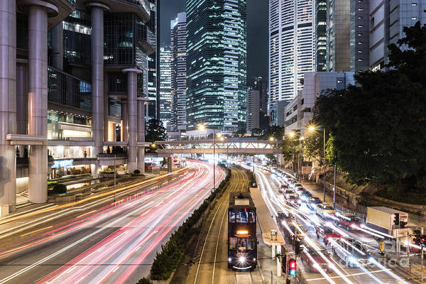 Photograph - Traffic Rushing In Hong Kong Island While A Tram Car Wait. by Didier Marti