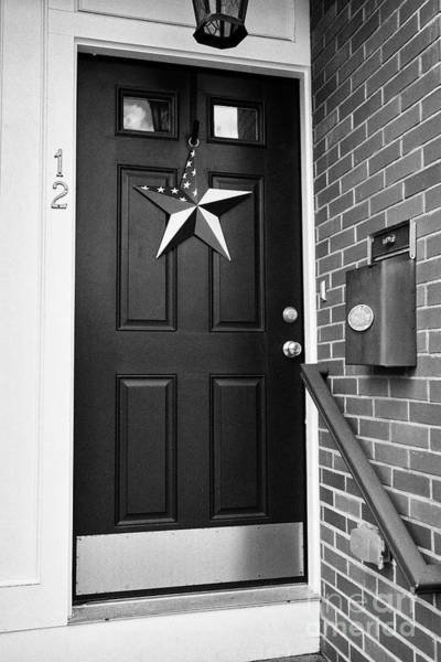 Wall Art - Photograph - us tin american flag ornament hanging on a door in historic area of Boston USA by Joe Fox