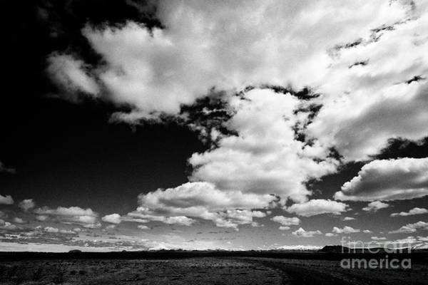 Wall Art - Photograph - white clouds in blue sky over dirt track into the wilderness in open farmland in southern Iceland by Joe Fox