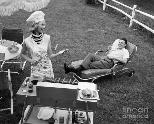 Service Dog Photograph - Woman Grilling Hot Dogs For Man by Debrocke/ClassicStock