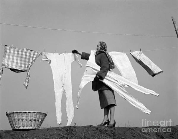 Wall Art - Photograph - Woman Removing Frozen Clothes by Debrocke/ClassicStock