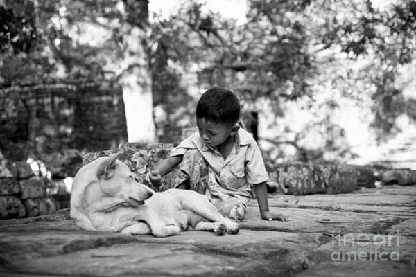 Photograph - Cambodian Boy Near Some Ruins Playing With His Dog. by Joaquin Corbalan