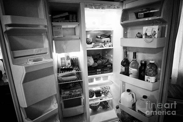 Wall Art - Photograph - doors open of a well stocked large us kitchen fridge freezer USA United States of America by Joe Fox